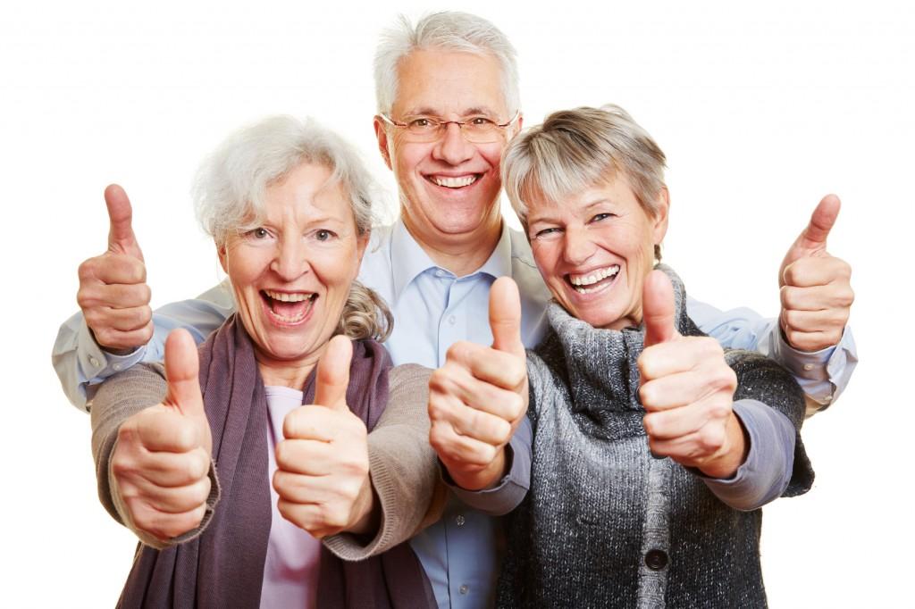 Drei attraktive Senioren halten glücklich ihre Daumen hoch