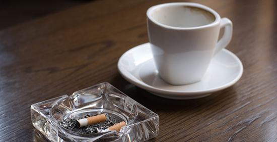 Ashtray and empty coffe cup on the cafe table. SFocus on the cigarette butt.